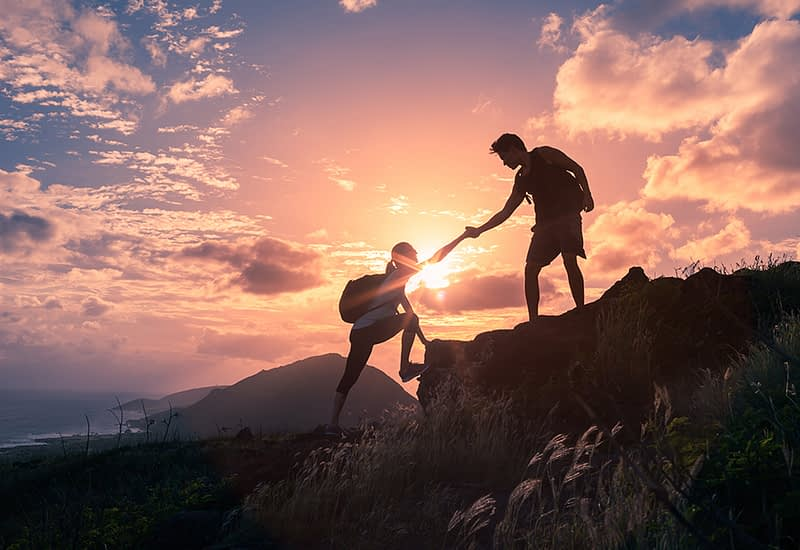 Mies auttaa naista kiipeämään kalliolle auringonlaskussa
