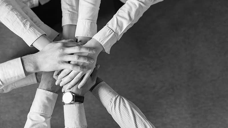 Liikemiesten- ja naisten kädet yhdessä
